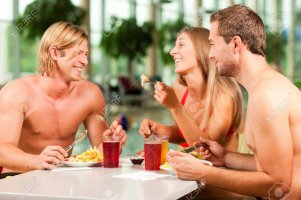 10770030-three-young-people-woman-and-two-men-eating-and-drinking-in-a-restaurant-at-a-public-...jpg